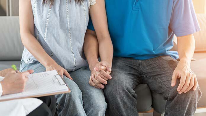 Trzymająca się za ręce para podczas leczenia niepłodności u endokrynologa